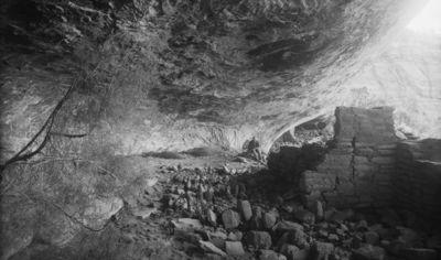 Wetherill's mesa, Mountain Sheep Canyon (Rock C.), Long House. Long Housen luolan sisustaa kuvattuna kivan 31 takaa, seinämä kuuluu rakennelmaan 33. Etualalla irtokiviä, taustalla kalliokielekkeen alla istumassa Al Wetherill