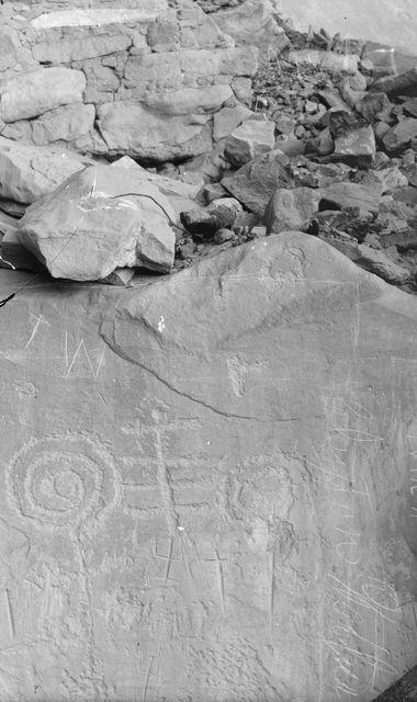 Wetherill's mesa, Long Canyon (Mancos C.), Step House. Kalliopiirroksia Step Housen seinässä. Kuvan ylälaidassa osa seinämuuria, sen alapuolella yhtenäinen kivipinta, jossa mm. ihmishahmoja. Oik. reunassa Clayton Wetherillin allekirjoitus