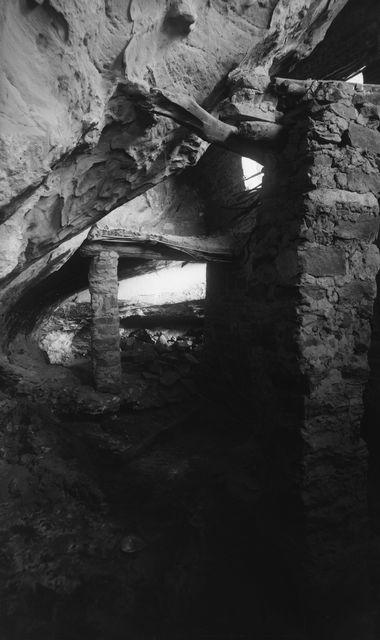 Wetherill's mesa, Spring House Canyon (Long Canyon), Spring House. Spring Housen luolan lähinnä kalliota oleva osa, jossa sijaitsee lähde. Oik. lähes kallionkielekkeen kattoon ulottuva muuri, joka on tuettu kallioon veistetyllä hirrellä