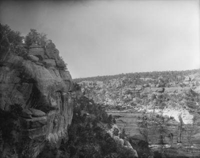 Chapin's mesa, Soda Canyon? Jyrkkäseinämäinen kanjoni, jonka seinämissä ei ole näkyvissä kallioasumuksia. Kanjonin reunoilla matalaa pensaskasvillisuutta. Vas. kallionharjalla pieni, pyöreä rakennelma