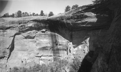 Chapin's mesa, Navajo Canyon, Square Tower House. Kallioasumus kuvattuna suoraan etelästä. Keskellä kuvaa monikerroksinen torni, jonka oik. puolella korkean kallioasumuksen rauniot, kauempana vas. leveähkö, matala raunio
