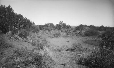 Wetherill's mesa, Mountain Sheep Canyon (Rock C.). Vesisäiliön rauniot Kodak Housen yläpuolella. Hiekasta ja kalliosta muodostuva aukea, jonka laidoilla kiertää laakeista kivistä tehty latomus. Raunion laidoilla kasvaa matalia puita ja pensaita