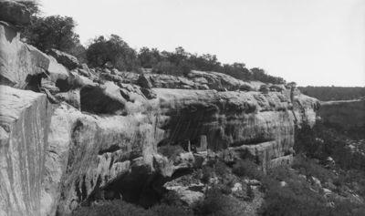Chapin's mesa, Spruce Canyon, Spruce Tree Lodge? Pieni kallioasumus kallionseinämällä. Rakennelma kaksiosainen, keskeltä matalampi. Vas. alhaalla isompi kallioasumus osittain näkyvissä