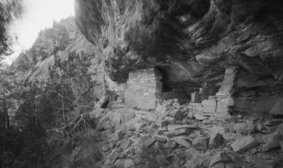 kallioasumuksen toinen pää, jossa kaksi rakennelmaa. Vas. pieni kallioasumus, joka ulottuu luolan kattoon, samoin oik. mutta tämä osittain sortunut. Raunioiden edessä paljon isoja siirtolohkareita, Vas. havupuita ja kanjonin seinämää