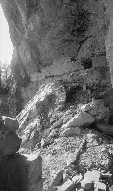 Wetherill's mesa, Mountain Sheep Canyon, Kodak House. Kodak Housen pohjoisosaa, keskellä kuvaa kallioasumukseen johtava oviaukko, jonka yläpuolella kallionseinämässä ikkunaton kivimuuraus. Etualalla paljon irtokiviä ja vas. kulmassa muurinkatkelma