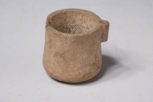 Малка чашка от кост с дръжка отстрани.