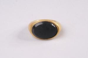 Златен пръстен с овален черен камък.