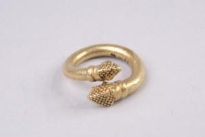 Златен пръстен. Масивна златна халка, на двата края на която има пирамидки от изпъкнали дребни зрънца.