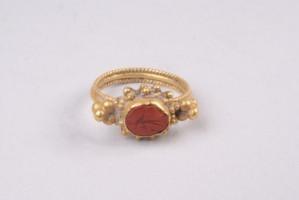 Златен пръстен с малко червено камъче, върху което грубо е моделирано изображение на Хермес. Около камъчето има групи от четири топчета. Халката е изработена отделно и по-късно прилепена.