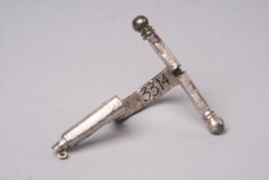 Сребърна фибула без игла. Украсена е с инкрустация с ниело. Има надпис на латински.