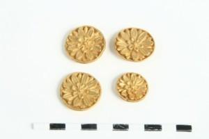 Четири апликации във форма на златни розети.