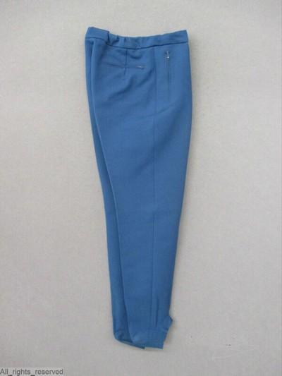 A.broek in petroleumblauw polyamide tricot, ritssluiting B. handgebreide wollen muts in wit en petroleumblauw, met opgemaasde bloemmotieven C. Zonnebril met bruin kunststof montuur