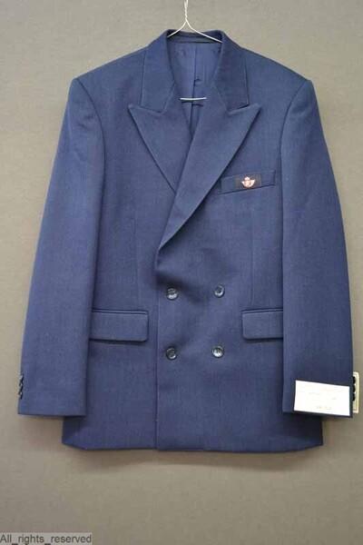 A. Blauwe broek in wol, polyester en polyamide, voor zomergebruik B. Vest in hetzelfde materiaal C. Lange parka in donkerblauw en rood, 100% polyamide D. korte parka in dezelfde stof E. Hemd met lange mouwen, in blauw en wit gestreept katoen F. Gelijkaardig hemd met korte mouwen G. Blauwe trui met V-hals in wol en acryl H. Gelijkaardige trui in wol met ronde hals I.J. Twee blauwe dassen met rode strepen K.L. Mitaines in wol en acryl M. Lange jas in polyester en katoen N. Pet