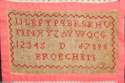 Merklap met een reeks naaioefeningen en borduurwerk; delen aan elkaar verbonden met roze polyamide voering; tekst : AV Broechem
