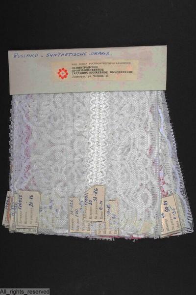 Stalenboek met witte en gekleurde stroken en tussenzetsels in machinale kant, uitgevoerd in polyamide