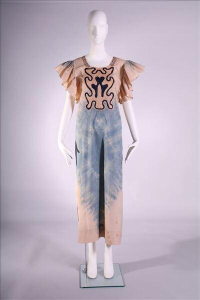 Jurk in beige met blauwe batik tekening. Ronde halsuitsnede en geplooide kapjes aan de armuitsnede. Op voorpand en aan de halsuitsnede borduurwerk in beige en blauw. Splitten aan de zijnaden.