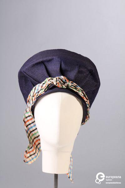 Hoed in blauw bandstro met geruite sjaal rond de bol