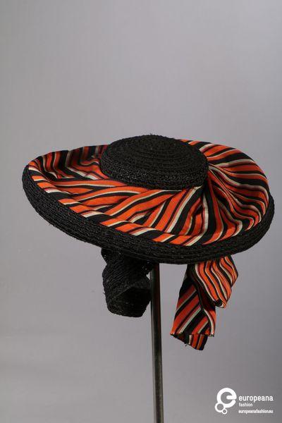 Zwarte hoed in stro met gestreepte stof tussen rand en bol