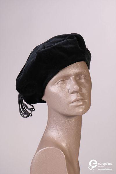 Fysieke beschrijving: Zwarte baret in fluweel met naden. Op de bovenkant is er een lange kwast gemaakt van linten. Contextuele beschrijving: Zwarte baret in fluweel met naden. Op de bovenkant is er een lange kwast gemaakt van linten.