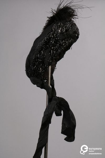 Kapothoed in zwarte raffia, bekleed met gitkralen, zwarte pailletten en veren