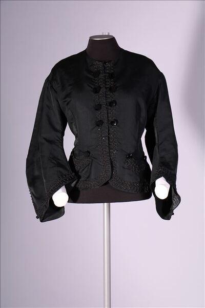 Corsage in zwarte zijde, afgewerkt met sierlint en parels