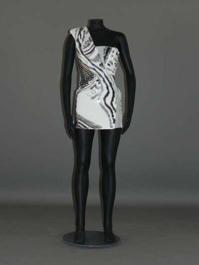 Miniabito in crepe di seta panna interamente ricamato con paiettes nei colori del bianco, argento e nero; fodera in twill di acetato e rayon color panna.