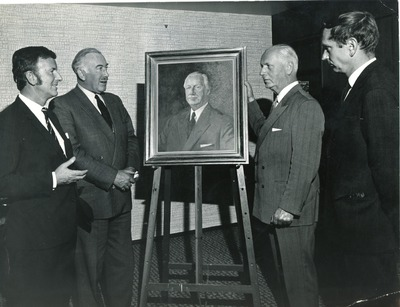 Gordon Lambert, Edward C. Bewley and others looking at a portrait of Bewley