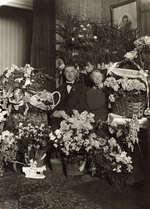 De beiaardier Jacob Vincent(1868-1953) samen met zijn vrouw gezeten tussen manden met versierde bloemboeketten ter ere van zijn 25-jarig jubileum als carillonspeler. [Amsterdam],1925.