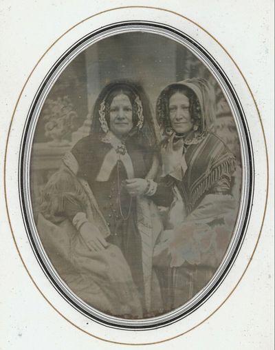Zwei Damen, Dreiviertelfiguren, in reicher Straßenkleidung, im Hintergrund Atelierdekoration