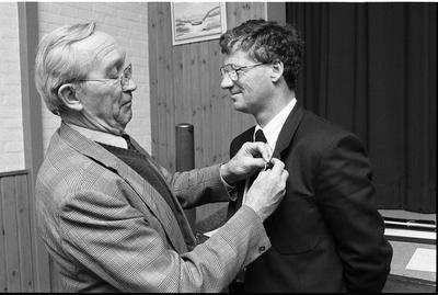 Bruinisse. Molenstraat. Rode Kruisgebouw. Kringcommandant van het Nederlandse Rode Kruis N. M. Bollen (links) spelt H. van den Bos uit Bruinisse de eremedaille in zilver op. Van den Bos neemt afscheid, na elf jaar actief te zijn geweest als secretaris van de plaatselijke Rode Kruisafdeling.