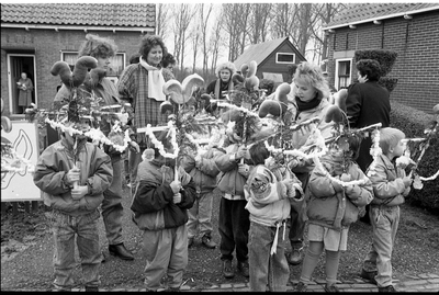 Ouwerkerk. Dorpsring. Leerlingen van de plaatselijke openbare basisschool gaan ter gelegenheid van Palmpasen door het dorp. Zij bellen aan bij inwoners van 80 jaar en ouder om hen een brooddeeghaan en -bloemetje aan te bieden.