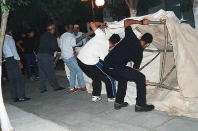 Άνδρες ετοιμάζονται να «ενδυθούν» την «Μπάμπω Τζαμάλα», για την τελετουργική περιφορά της στους δρόμους του χωριού.