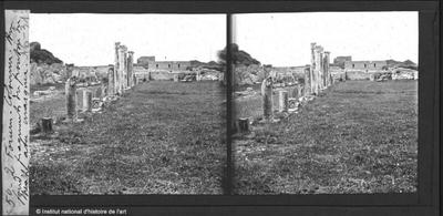 Forum. Colonne. Au fond, fragments du fronton du théâtre avec marque