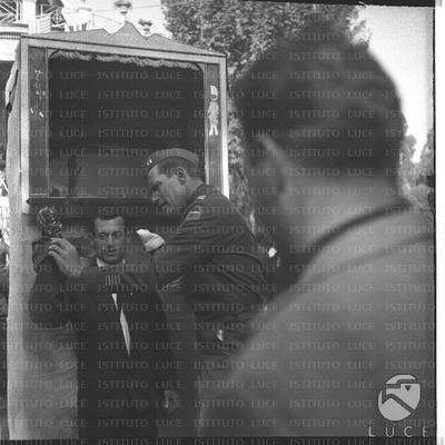 Charlton Heston in costume da tenente dell'esercito con un burattinaio al Pincio sul set del film 'Pranzo di Pasqua' - piano americano