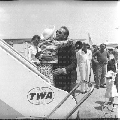 Charlton Heston abbraccia affettuosamente la moglie sulle scalette dell'aereo - piano medio