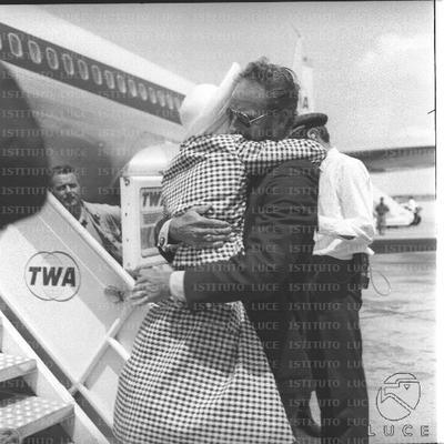 Charlton Heston abbraccia affettuosamente la moglie sulle scalette dell'aereo - piano americano