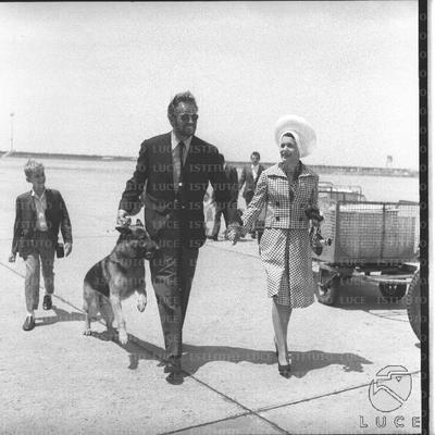 Charlton Heston con il cane al guinzaglio sulla pista dell'aeroporto seguito dalla moglie e dal figlio - totale