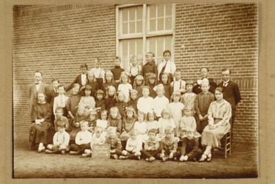 Onbekende klassefoto, met enkel de namen van de leerkrachten vermeld, rechts meester Frencken, hij ging later voor priester studeren en juffrouw Driessen, links meester Baets en juffrouw Gabriëls
