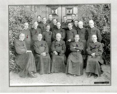 Bisschoppelijk College, groepsportret voor de ingangsdeur aan de Wilhelminasingel; 1. Piet Vullinghs (Frans), 2. Seelen  (later pastoor Venlo), 3. Franck (directeur), 4. Van Eys, 5. Houben, 6. Willems, 7. Pierre Evers (Nederlands), 8. Brummans (Aardrijkskunde), 9. Jules Nabben (Geschiedenis en provisor), 10. John Nievergeld (Wiskunde), 11. Piet Moors (Boekhouden, later predident Rolduc, daarna Bisschop van Roermond), 12. Nes(t) van den Bergh (Engels, bijnaam De Bums), 13. H. Jochems (Duits, later president Rolduc), 14. (E)mile Suilen (Klassiek Talen), 15. Wijnen, 16. Bèr Gubbels (Klassieke Talen, rector gymnasium), 17. Joske Janssen (Godsdienst), 18. Jaques Maes (Prefect van de internen, later pastoor Nederweert-Eind), 19. Thijssen