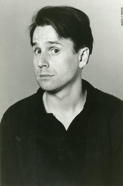 black and white head shot of a man in a black tshirt and jacket