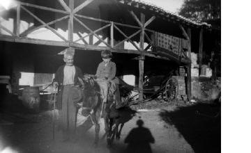 Ηλικιωμένος άνδρας και αγόρι σε γαϊδούρι σε αυλή σπιτιού. Γύρω στα 1935 Έλλη Παπαδημητρίου (ΦΑ_19_646)