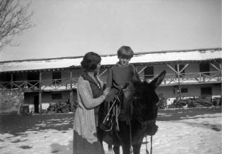 Γυναίκα και αγόρι σε γαϊδούρι σε αυλή σπιτιού. Γύρω στα 1935 Έλλη Παπαδημητρίου (ΦΑ_19_647)