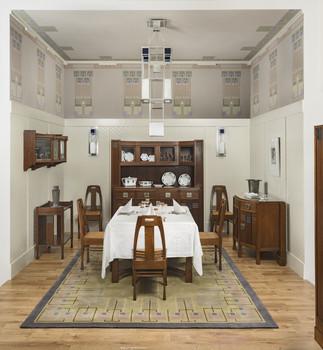 Speisezimmer-Ensemble (Wertheim-Zimmer): Tisch, 5 Stühle, Büffet, Eckschrank (nicht im Bild), Anrichte, Beistelltisch, Hängeschrank (Originale); Deckenlampe,  2 Wandlampen, Teppich (Reproduktionen)