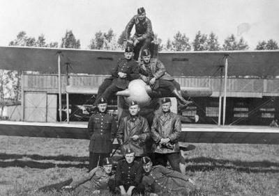 Siužetinė. Grupė 4-osios eskadrilės lakūnų prie LVG C VI lėktuvo Aleksoto aerouoste. Iš kairės sėdi: A. Plaušinaitis, J. Pyragius, V. Bartuška. Stovi: V. Jablonskis, eskadrilės vadas L. Peseckas, S. Darius. Virš jų: A. Damijonaitis, J. Liutkus, V. Tiškus.