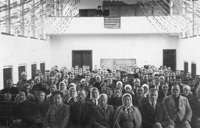 """Siužetinė. Pradinės mokyklos """"Aušra"""" salės vaizdas. Tarybų valdžios šalininkų susirinkimas. Balkono centre pakabintas Juliaus Janonio eilėraščio ketureilis: Minėkim ne pragaištį, mirtį, kapus, /Bet kovą, vien kovą be galo! /Geresnio paminklo didvyriams nebus, /Kaip vykdymas jų idealo! J.Janonis."""