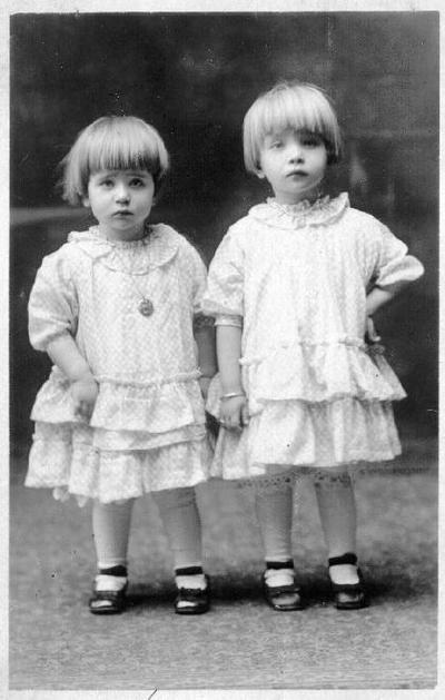 Grupinis portretas. Dvi mergaitės šviesiomis suknelėmis.Iš kairės: Stela (g.1917)ir Onutė Atlavinytės (1916 12 18 Klivlende–1991 02 24 Vilniuje. Palaidota Biržuose, šalia tėvų Liepų g. kapinėse). Tėvai Atlaviniai, kilę nuo Papilio, laimės ieškojo už Atlanto. Dirbo skerdykloje. Amerikoje abu susituokė. Ilgai svečioje šalyje neužsibuvo, nes netiko klimatas. Į Lietuvą su Amerikoje gimusiomis dukromis Onute ir Stefanija sugrįžo 1921 m. Seserų vaikystė prabėgo Mikalių kaime. Onutė Atlavinytė, habilituota biologijos mokslų daktarė. Baigusi pradžios mokyklą, 1932–34 mokėsi Joniškėlio žemės ūkio mokykloje. Vėliau baigė Vilniaus pedagoginį institutą, dėstė Telšių pedagoginėje mokykloje, dirbo Vilniaus pedagoginiame institute. 1959 m. įstojo į aspirantūrą Mokslų akademijos Biologijos institute. Apgynė biologijos mokslų kandidatės disertaciją, 1979 m. Taline jai buvo suteiktas biologijos mokslų daktarės vardas. Tais pačiais metais gavo nusipelniusios mokslo veikėjos vardą, o 1986 m. mokslininkė tapo Respublikinės premijos laureate. Kartu su Onute Mokslų akademijos Zoologijos ir parazitologijos institute dirbę mokslininkai teigė, kad ji yra puiki dirvožemio zoologijos specialistė, nenuilstamai dirbusi mokslinį darbą, eksperimentavusi, ruošusi aspirantus mokslinei veiklai, mokslo žinias propagavusi spaudoje. Išleido knygą Sliekai - žemdirbio talkininkai, parašė dar dvi knygas, daugiau kaip 100 straipsnių, buvo ne vieno mokslinio darbo bendraautorė. Vasaras praleisdavo Dotnuvoje, atlikdama mokslinius darbus. Sesuo Stefanija ištekėjo už Povilo Jankūno, gyv. Biržuose).
