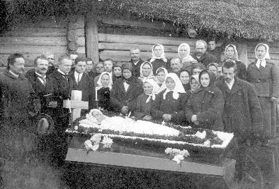 Siužetinė. Nežinomos moters laidotuvės. Su velione atsisveikina prie namų. Prie karsto iš kairės: Katrė Skeberdytė - Burbulienė (1888–1972) iš Šimpeliškių, Otilija Burbulytė, Jurėnienė, Užunarienė, Ona Užunarytė (Šimpeliškiai). Iš kairės trečias - kanklininkas Petras Lapienė.