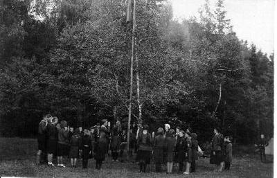 Siužetinė. Skautų stovykloje keliama vėliava. Dešinėje - Biržų gimnazijos mokytoja Marija Bernšteinaitė (balta berete). Nuo 1935 m. Mirgos draugovės vadovė, jaunesniųjų skaučių skyriaus vedėja, vadovavusi ir 1937 m. įsteigtam tuntui.