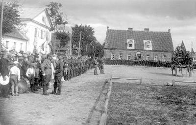 Siužetinė. Stanislovo Dagilio (Aptiekos aikštė). Šventės dalyviai, priekyje iš kairės pirmas Pranas Lukoševičius (1898—1936). Tribūna puošta žolynais, vėliavomis ir Vytauto Didžiojo portretu. Kairėje Baltoji vaistinė, tiesiai - Žydų liaudies bankas.