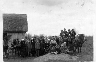 Siužetinė. Grupė žmonių Dirvonakių k.(?). Priekyje iš kairės ketvirtas - berniukas, Erikos Variakojytės brolis Vilius, vienas žmogus su armonika, kitas - elgeta (ubagas). Du arkliais pakinkyti vežimai. Matyti namo, dengto šiaudiniu stogu, kampas ir prikalta lentelė su įrašu M 21 (?)....